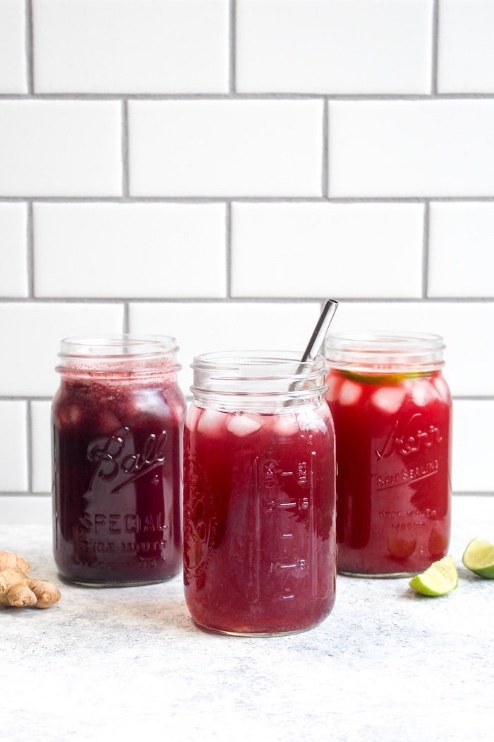 three mason jars filled with red smoothies garnished with lime slices ice how to detox your body ginger and lime on the side