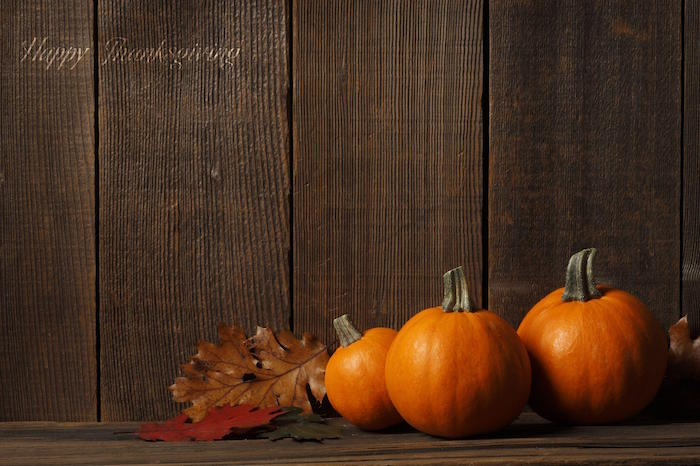 three pumpkin with three fall leaves in brown green orange on wooden surface cute thanksgiving wallpaper
