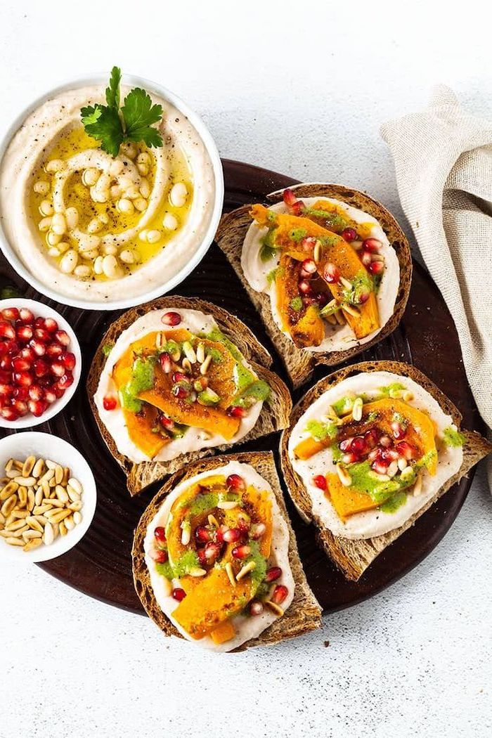 toast with sweet potato wedges hummus pomegranate seeds arranged on brown plate vegan appetizers white bowl full of hummus
