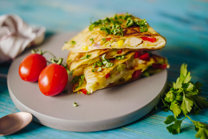 traditional mexican food quesadilla with chicken tomatoes corn garnished with chopped parsley two cherry tomatoes on the side