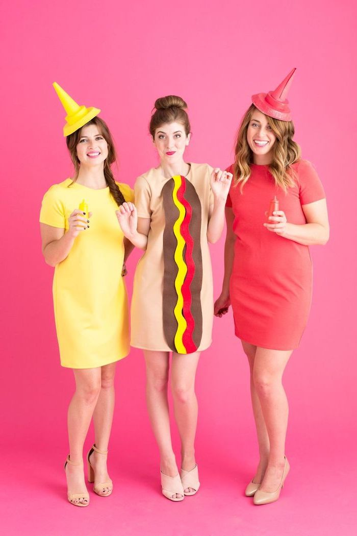 trio halloween costumes three women one dressed as bottle of mayo another as ketchup woman in the middle as hot dog