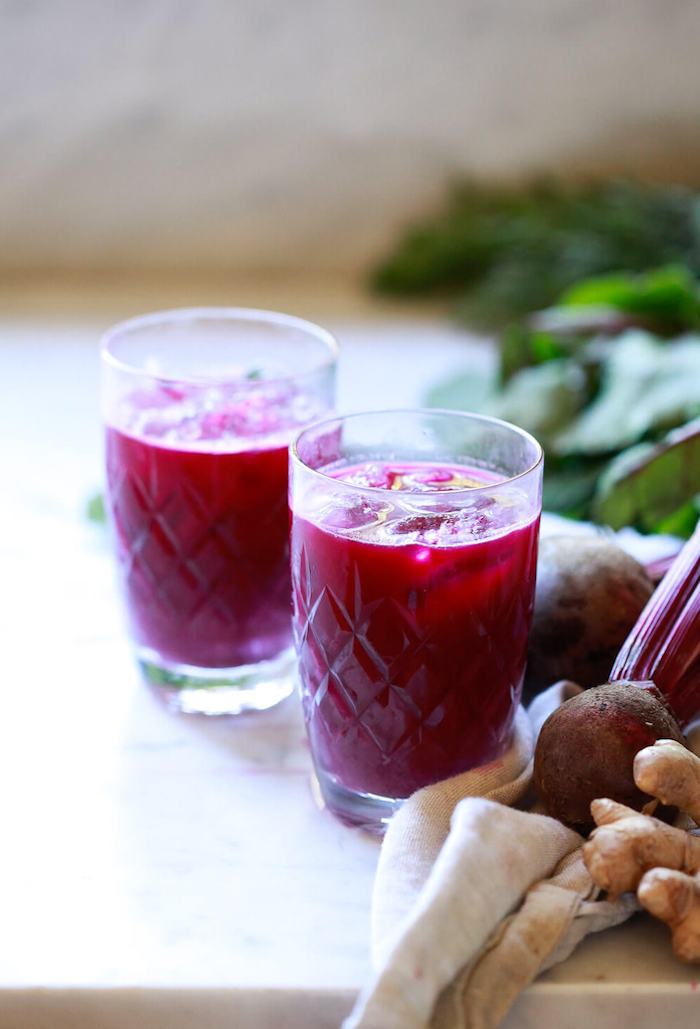 two glasses filled with beet juice placed on marble surface detox drinks for weight loss ginger and beetroot on the side