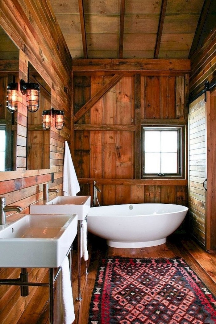 two sinks with mirrors and lamps hanging above them modern farmhouse bathroom wooden floor ceiling and walls with barn door modern farmhouse bathroom small rug on the floor