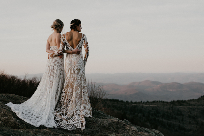 two women wearing all lace white dresses plus size beach wedding dresses photographed standing on a hill hugging