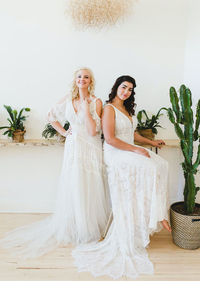 two women wearing all lace white unique wedding dresses sitting on tall chair green plants around them
