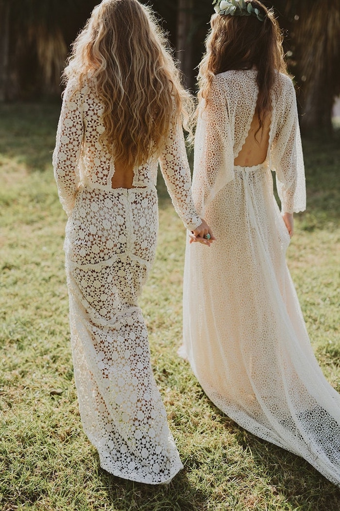 two women with long hair wearing all lace white long dresses holding hands boho beach wedding dress