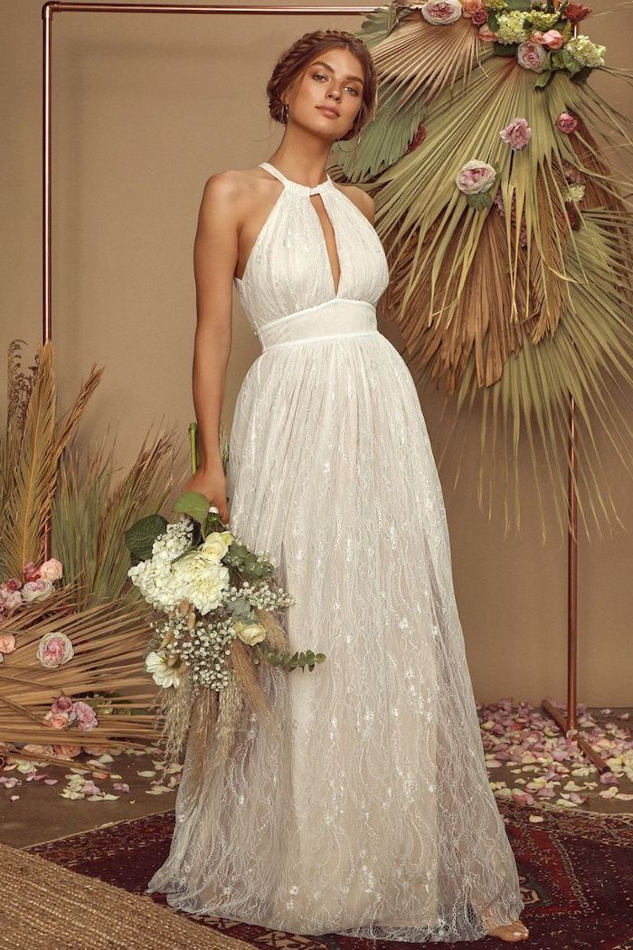 unique wedding dresses woman with dark blonde hair in low updo wearing tulle and lace white wedding dress holding white flower bouquet