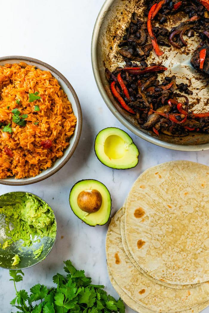 vegan burrito ingredients arranged on marble surface popular mexican food guacamole avocado rice tortillas