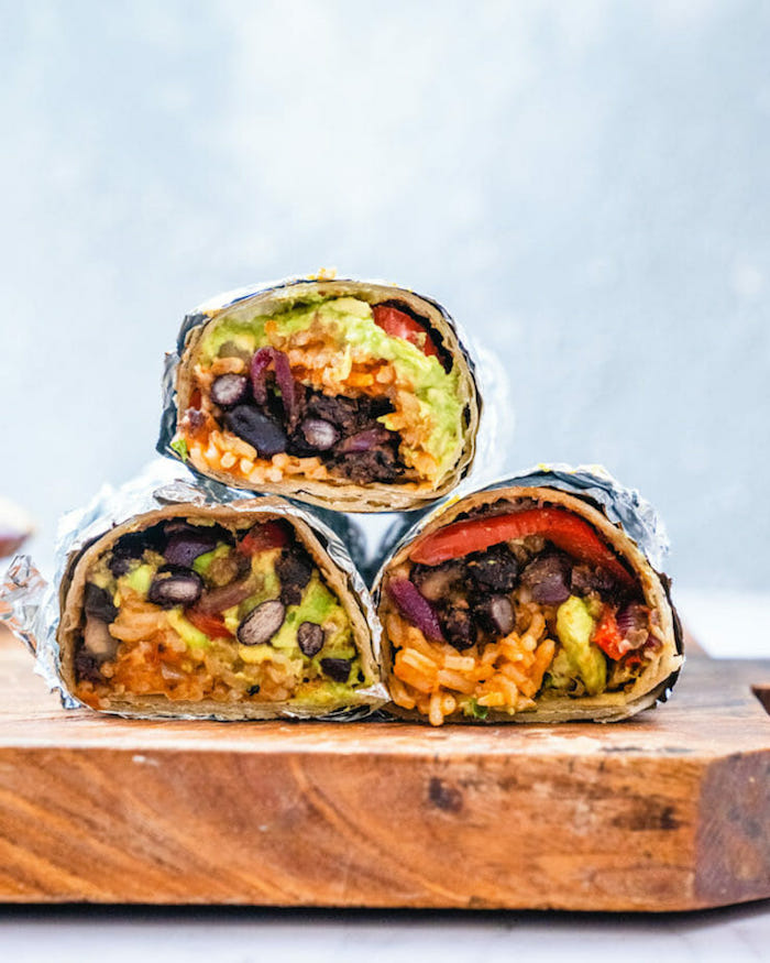 vegan burritos wrapped in foil popular mexican food arranged on wooden cutting board
