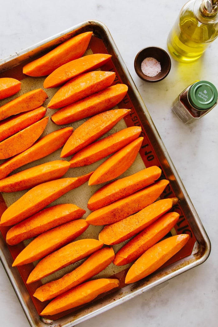 vegan party appetizers sweet potato wedges arranged on paper lined baking sheet covered with salt pepper olive oil