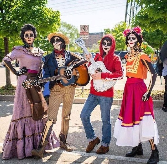 white and brown guitars held by two men two women next to them group halloween costume ideas four people dressed as characters from coco