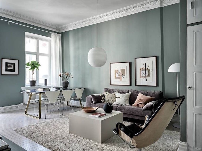 white coffee table gray sofa black leather armchair scandinavian interior design dark green walls dining table with white chairs