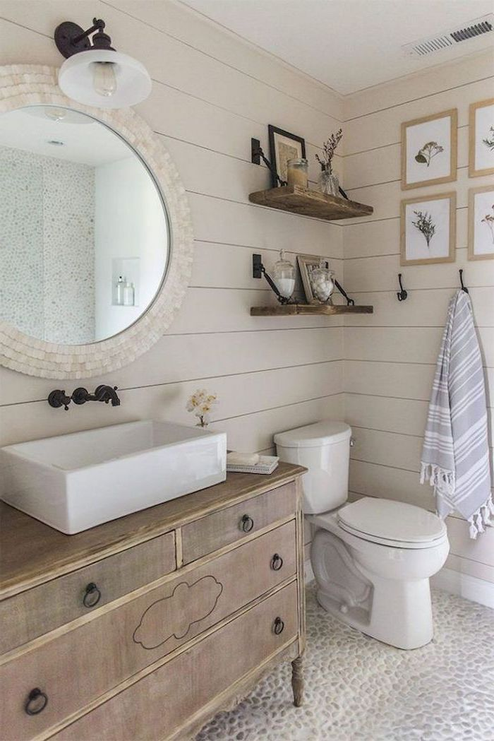 white shiplap on the walls cobble stone on the floor farmhouse bathroom decor wooden vanity round mirror above it two shelves above the toilet