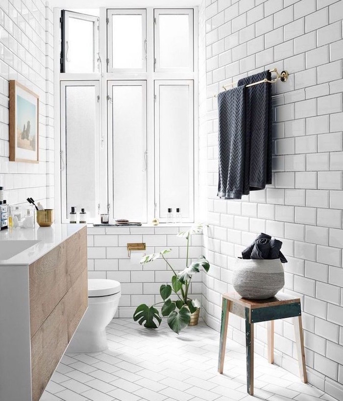white subway tiles in small bathroom with floatinf wooden vanity scandinavian furniture small vintage wooden chair