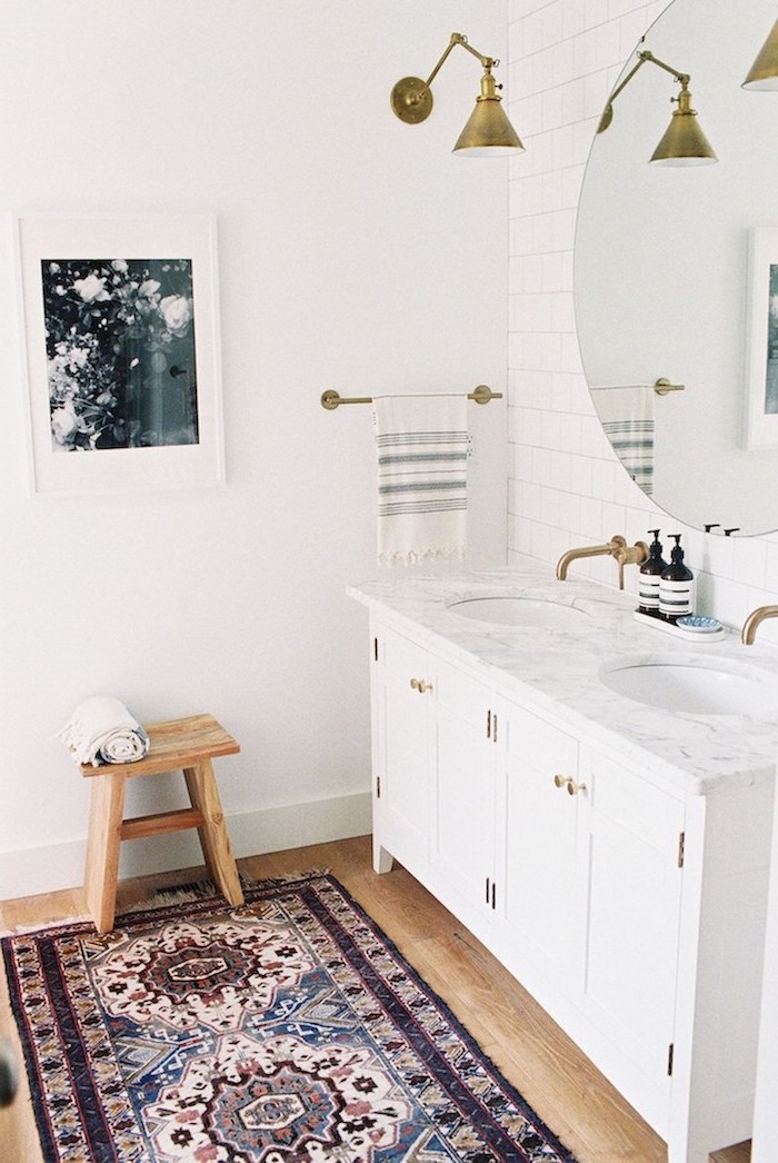 white vanity with two sinks large round mirror hanging above them on wall with white tiles modern farmhouse bathroom small rug on wooden floor