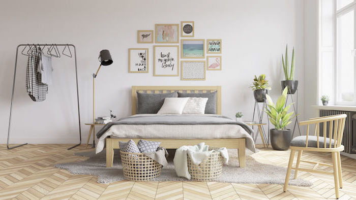 white wall with framed art hanging above bed with woden frame scandinavian home decor white rug on wooden floor