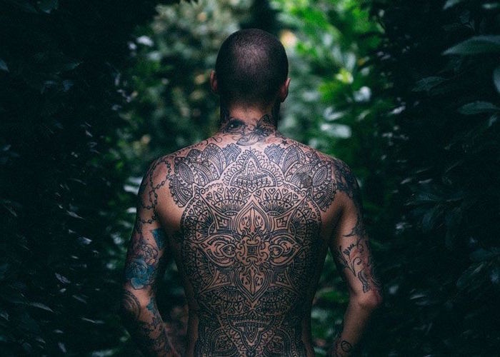whole back tattoo on man standing in the middle of forest simple tattoos for men maori tattoo
