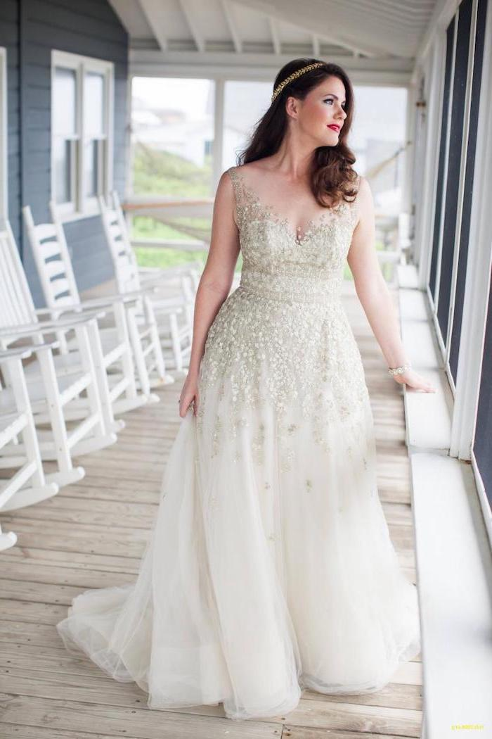 woman standing on a porch with medium length brown wavy hair long sleeve boho wedding dresses made of tulle and lace