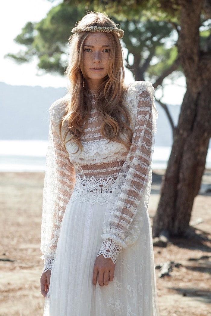 woman wearing long sleeve boho wedding dresses made of lace and tulle with long blonde wavy hair flower crown