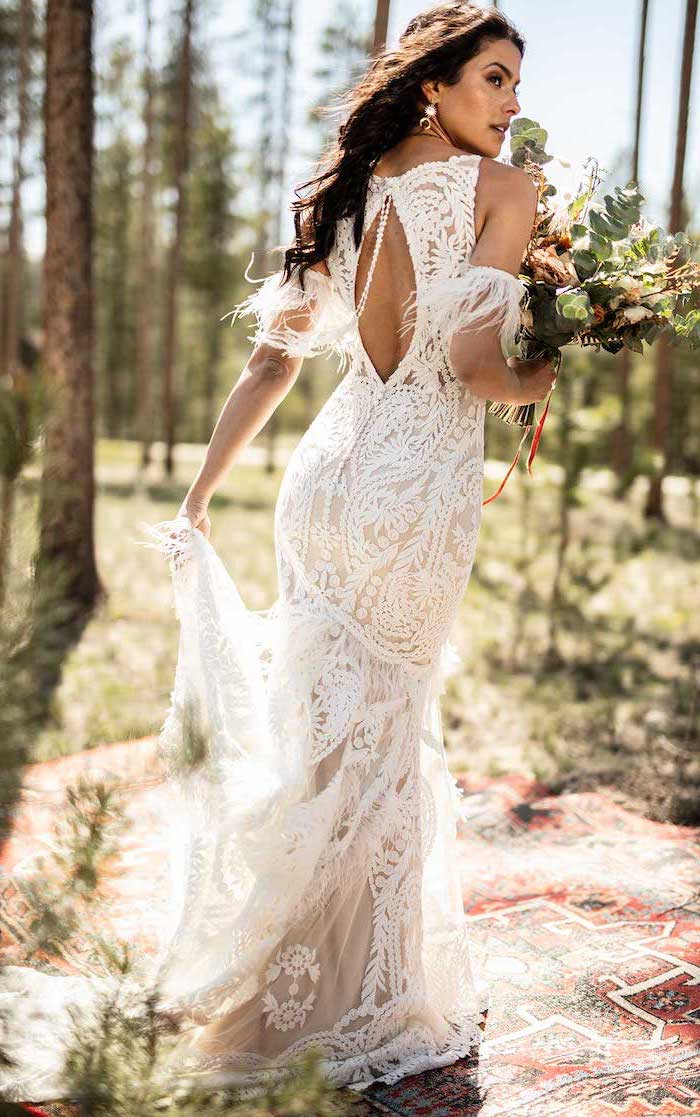 woman with long black wavy hair long sleeve boho wedding dresses wearing dress made of lace holding a large bouquet