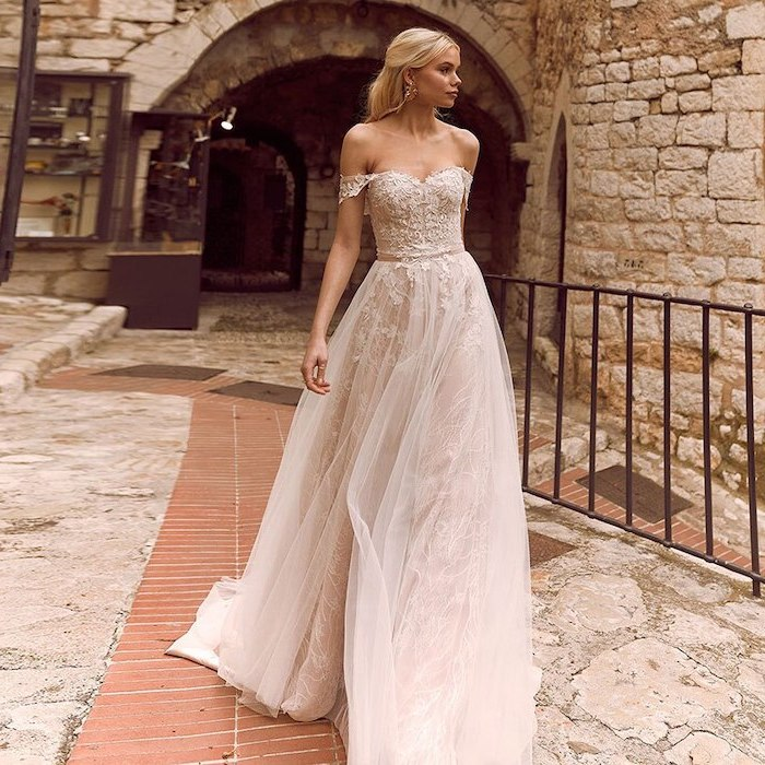woman with long blonde hair wearing sleeveless white boho lace wedding dress with bottom skirt made of tulle