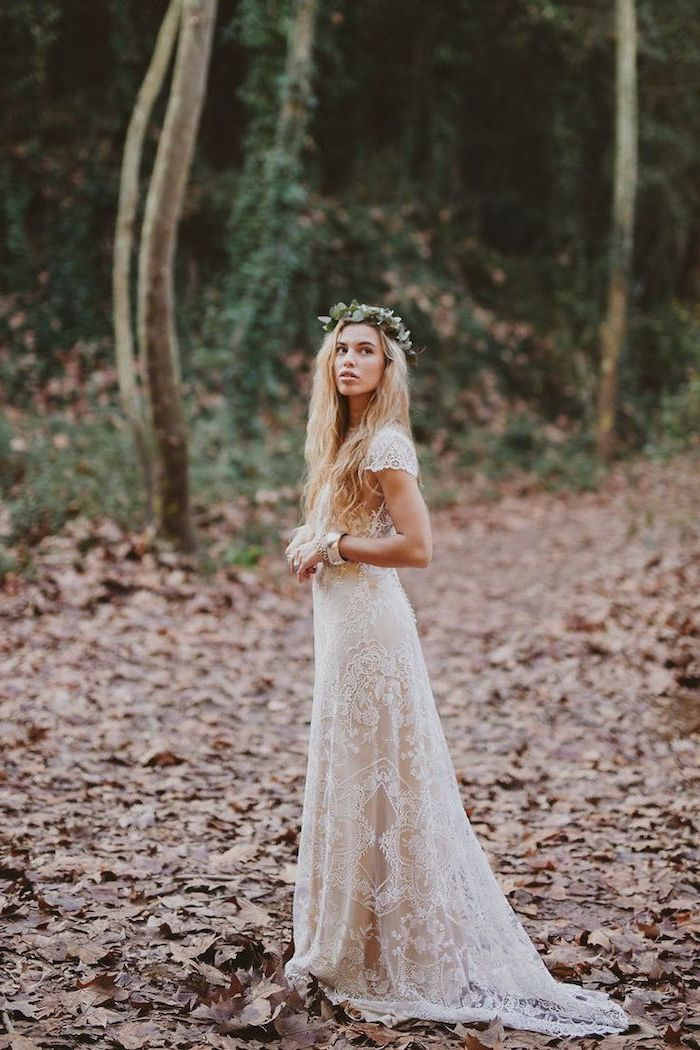 woman with long blonde wavy hair wearing all lace white bohemian wedding dress floral crown on her head