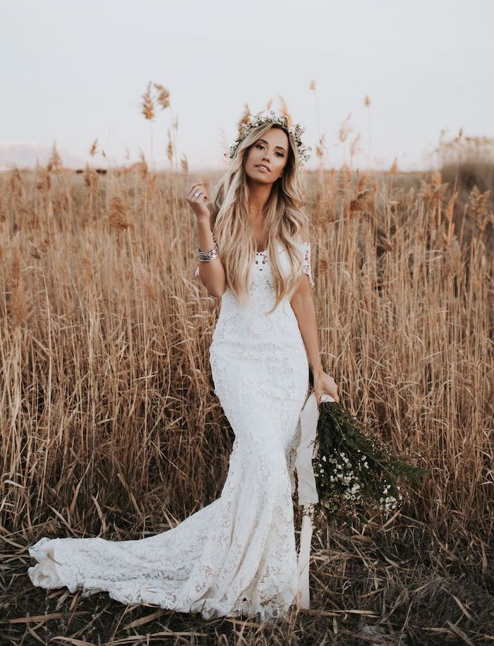 woman with long blonde wavy hair wearing floral crown plus size boho wedding dress wearing all lace white dress