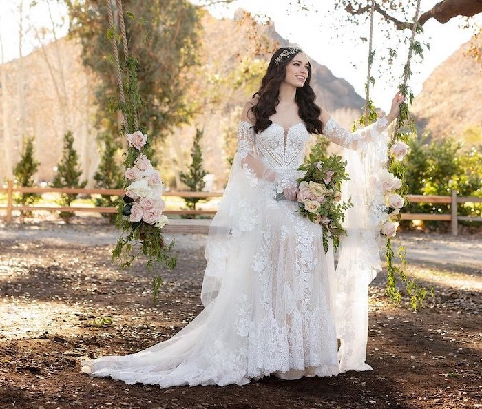 woman with long wavy black hair sitting on a wooden swing boho beach wedding dress wearing all white lacy dress with long sleeves