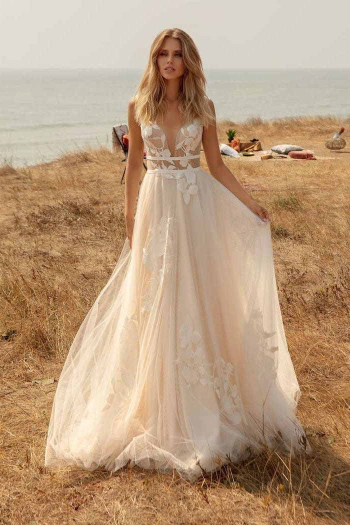 woman with long wavy blonde hair wearing flowy wedding dress made of tulle and lace photographed in a field