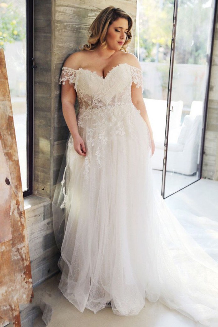 woman with medium length blonde curly hair wearing white dress with bottom skirt made of tulle lacy top plus size boho wedding dress