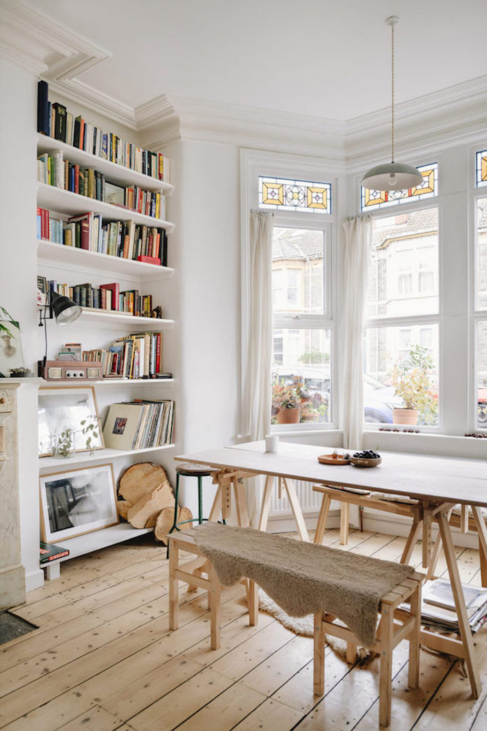 wooden dining table with wooden benches scandinavian design living room bookshelf in the wall white walls and wooden floor