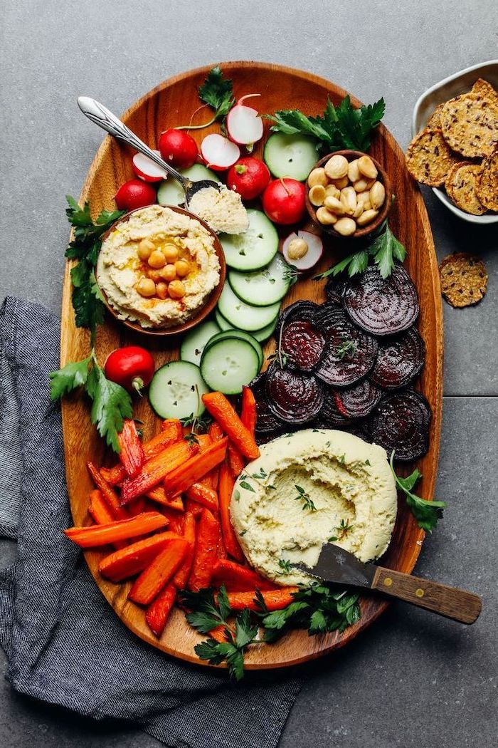 wooden tray full of different vegetables vegan appetizers two bowls of hummus garnished with parsley