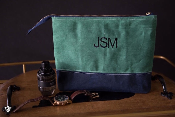 accessories bag made from blue and green velvet fabric good gifts for dad personalised with initials placed on wooden surface