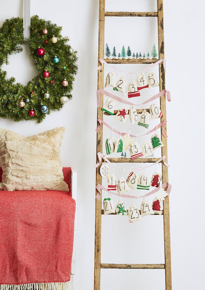 advent calendar ideas wooden ladder red and white ribbons tied from one end to the other small bags hanging from them