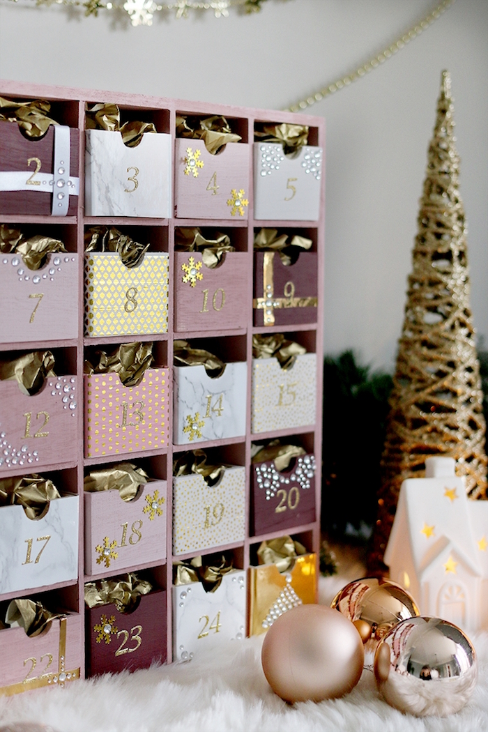 advent calendar in pink purple white and gold diy advent calendar ideas placed next to small faux golden christmas tree and baubles