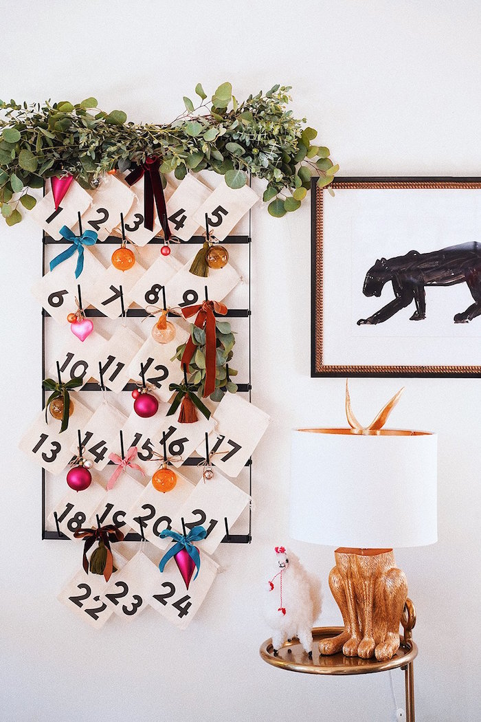 advent calendar small paper bags hanging on black metal rails hanging on white wall decorated with different ribbons
