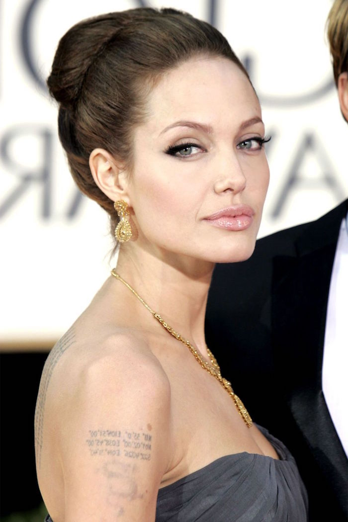 angelina jolie on the red carpet wearing grey dress hair in high updo winged eyeliner gold earrings necklace
