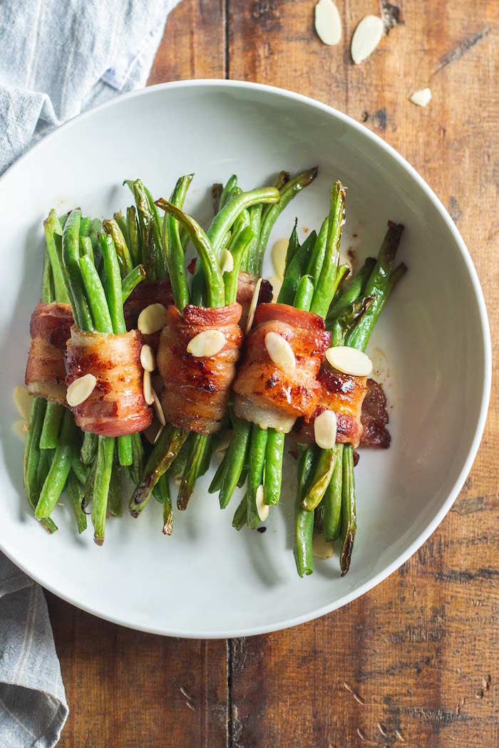 bacon wrapped green beans served on white plate with silvered almonds christmas food ideas placed on wooden surface