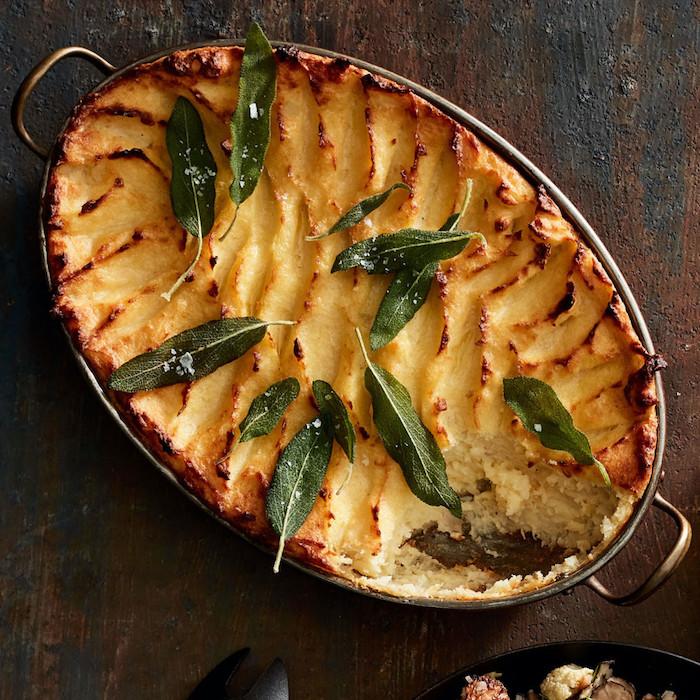 baked potato mash with fried sage leaves thanksgiving side dishes 2020 casserole placed on wooden surface