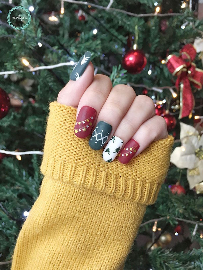 baubles on christmas tree in the background holiday nail designs in red white green matte nail polish with christmas inspired decorations