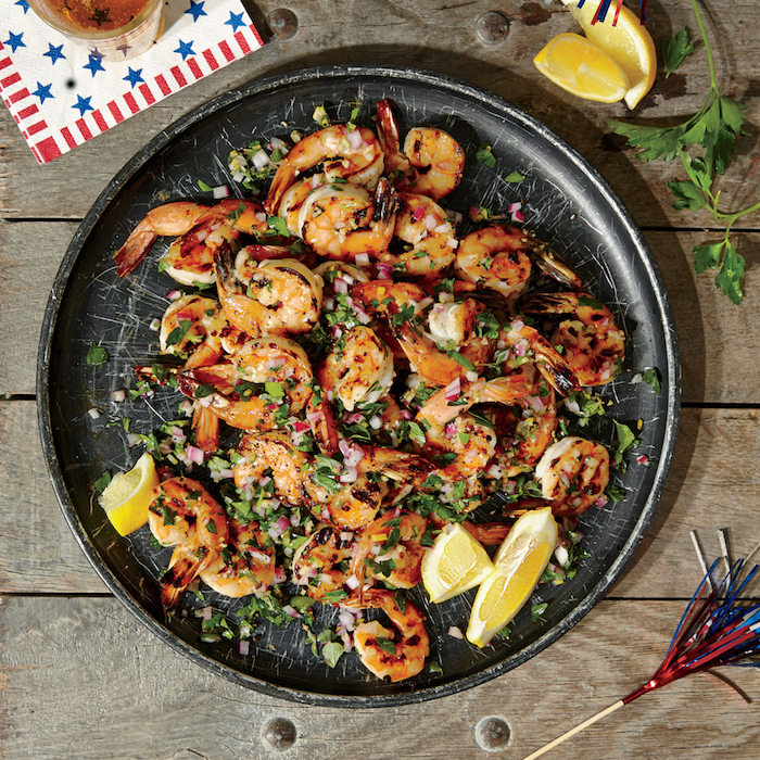 black ceramic plate with herbed grilled shrimp garlic shrimp recipe garnished with chopped parsley onion lemon wedges