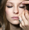 black eyeliner being drawn onto womans eyes how to do winged eyeliner woman with long brown wavy hair