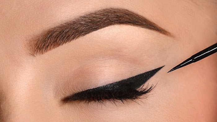 black eyeliner with sharp edge on closed eye winged eyeliner for hooded eyes close up photo of eye and thick eyebrow
