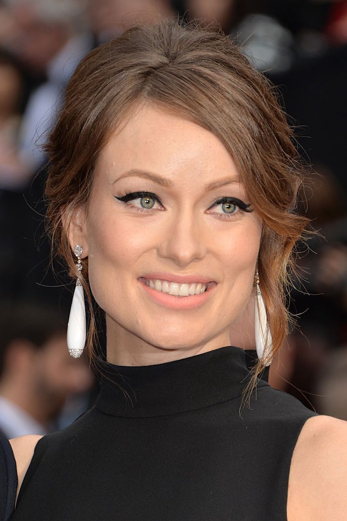 black satin dress worn by olivia wilde on the red carpet winged eyeliner brown hair in low updo white earrings