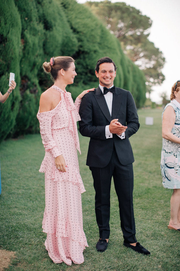 black suit worn by man standing next to woman wearing long pink dress with fringe black dots and long sleeves womens wedding guest dresses