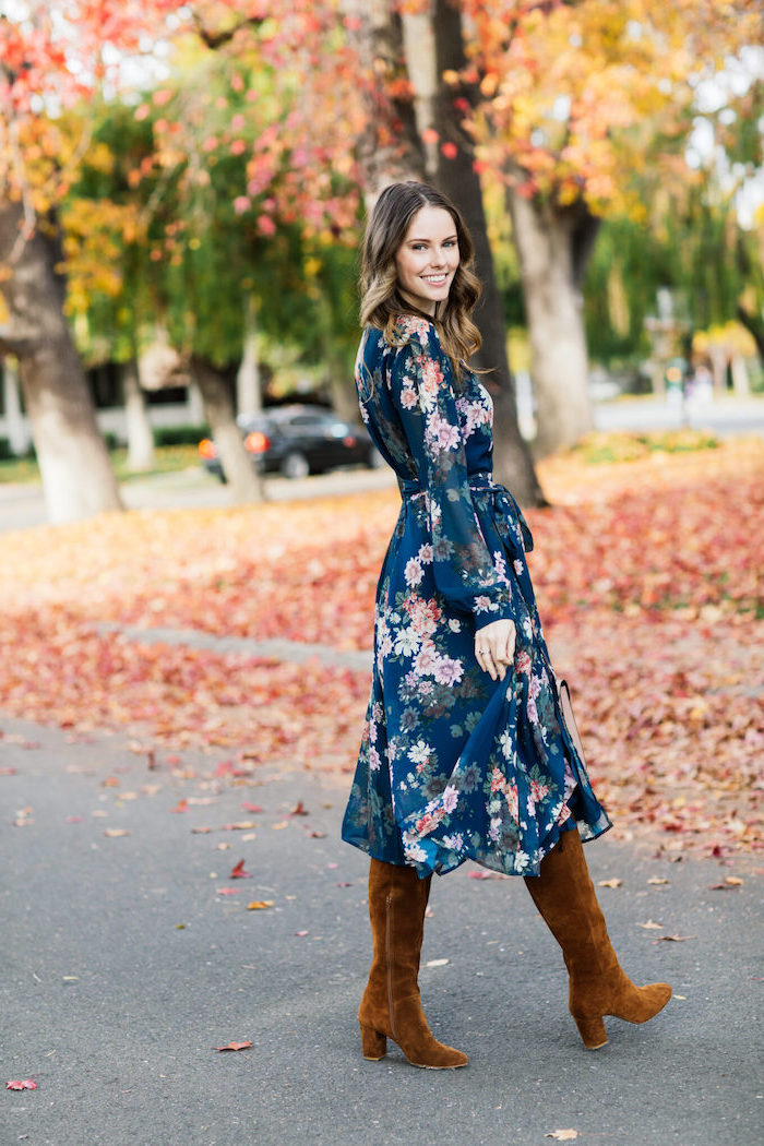 blue dress with pink flowers and long sleeves worn with brown velvet boots affordable wedding guest dresses woman with medium length brunette hair