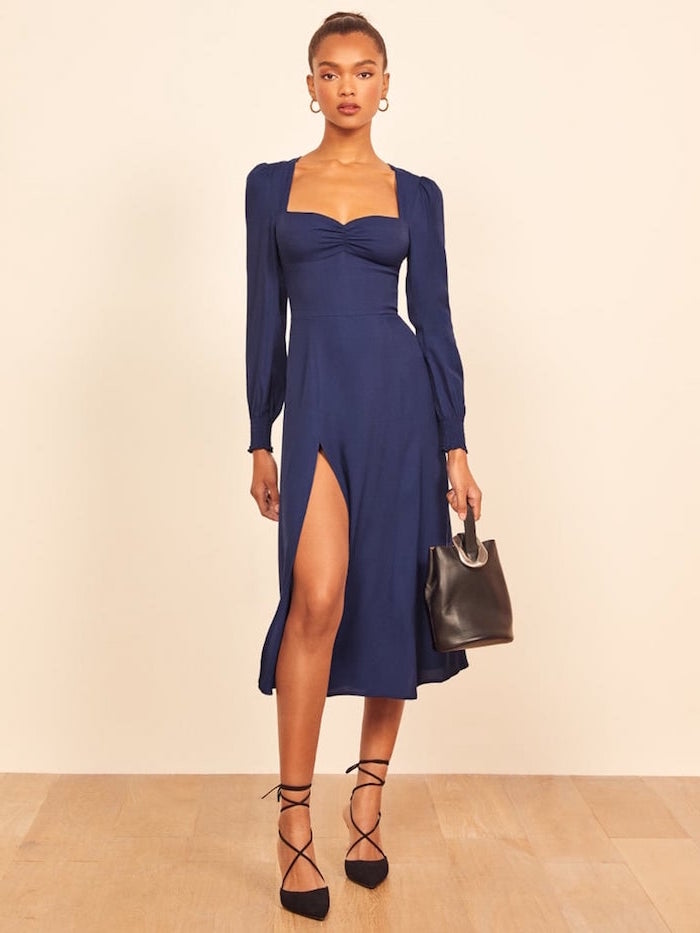blue dress with slit and long sleeves worn by brunette woman elegant dresses for wedding guests with black shoes and bag