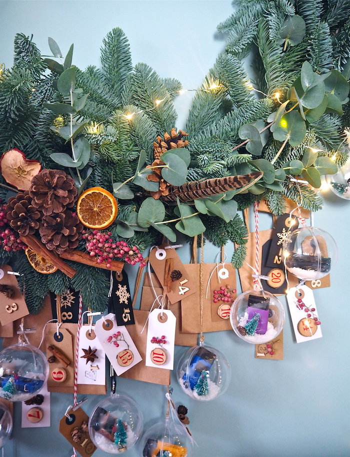 blue wall green wreathhanging on it advent calendar ideas small bags with paper tags hanging from the wreath with small transparent baubles