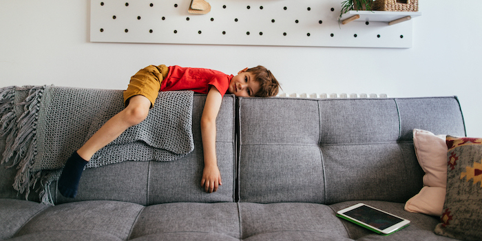 boy laying on the back of gray sofa wearing red t shirt mustard yellow pants indoor activities for kids