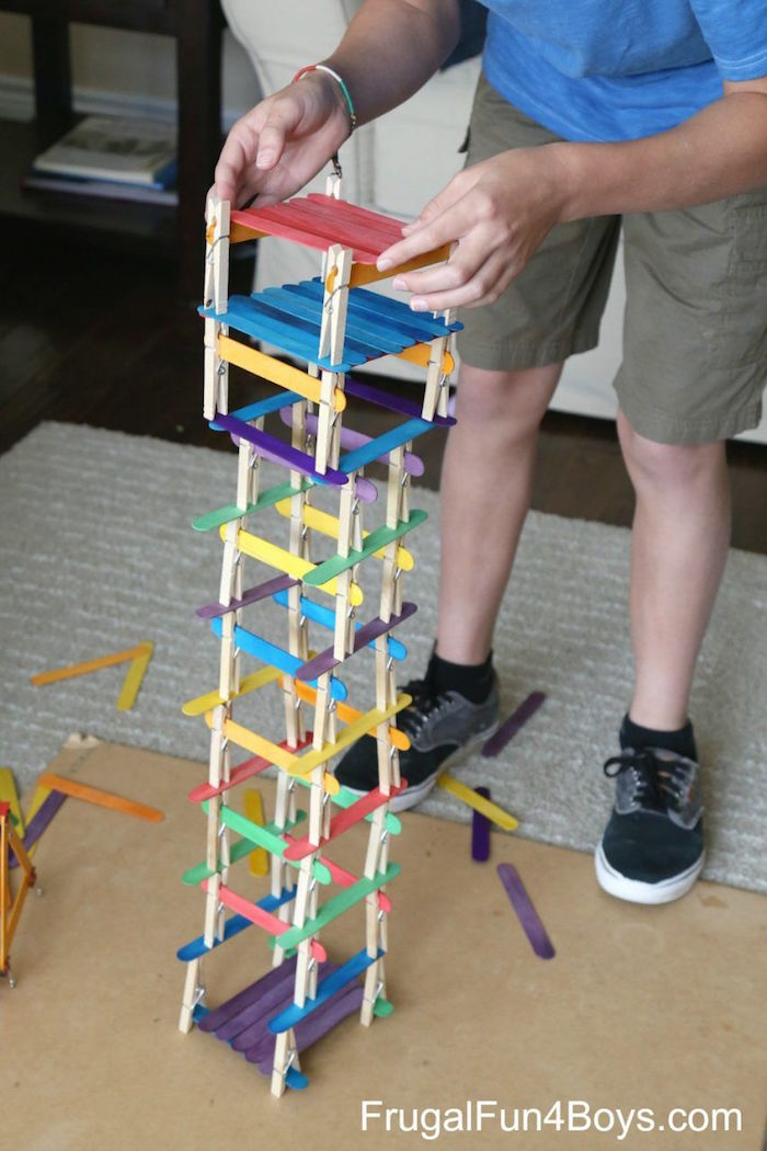 boy standing next to tower built out of clothespins and popsicle sticks craft ideas for kids in different colors
